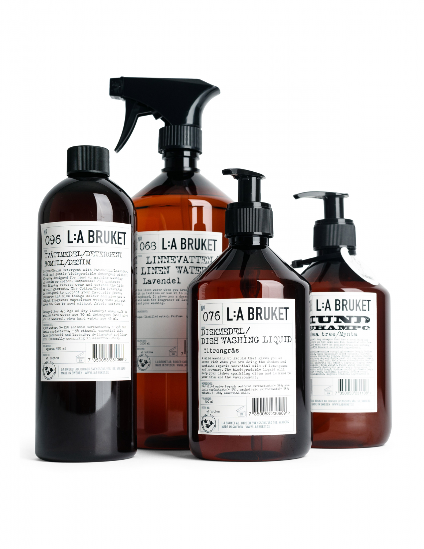 Fyra bruna flaskor i grupp, innehållande hemrengöring från L:a Bruket i olika storlekar.