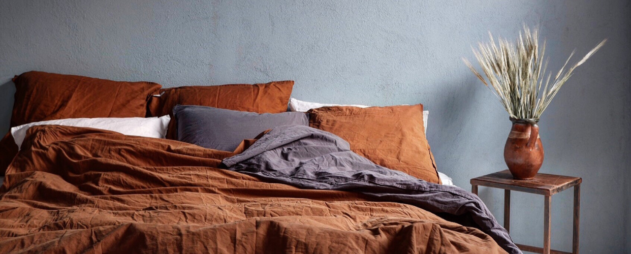 Säng i sovrum med ekologiska sängkläder i kummin och mörkgrå