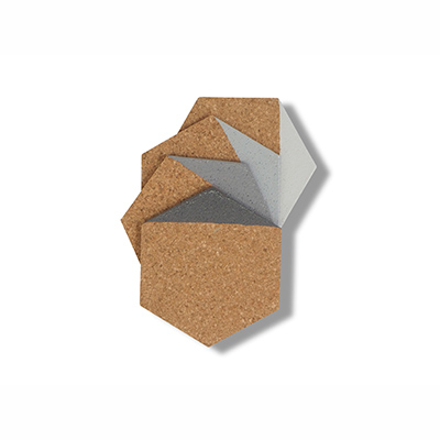 Coasters in hexagon made of light cork dipped in grey color.
