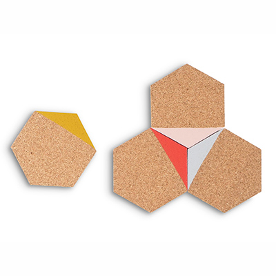 Coasters in hexagon made of light cork dipped in the color mustard, coral, grey and pink.