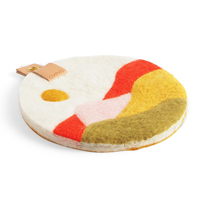 Round trivet with a hanger in eco leather and a motif of a field of Skåne in red, yellow and green colors..