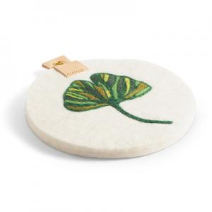 Round trivet with a hanger in eco leather and a motif of a green ginkgo leaf.