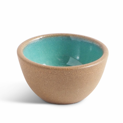 Small ceramic bowl with raw ceramics on the outside and turquoise glazing inside.