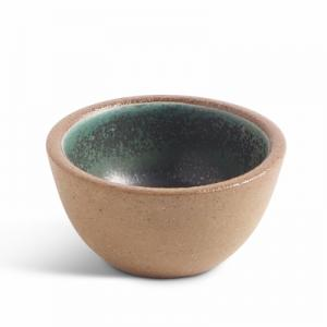 Small ceramic bowl with raw ceramics on the outside and teal glazing inside.