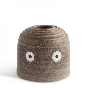 Ceramic vase in raw clay with eyes.