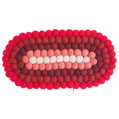 Oval trivet in 100% wool in red and pink hues.