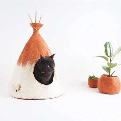 Grey cat inside a wool tipi in terracotta and white color.