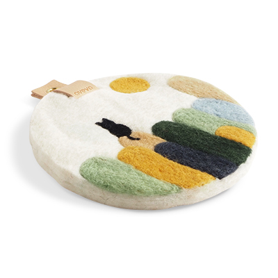 Round trivet with a hanger in eco leather and a motif of hills and a cat.