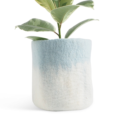 Large flower pot in light blue and white, made of wool with ombre effect, with a plant inside.