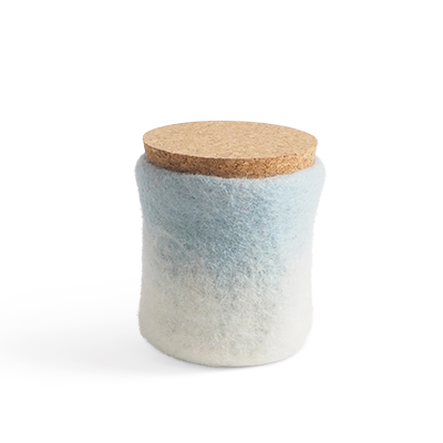 Handmade jar made of wool in light blue and white ombre with a lid of light cork.