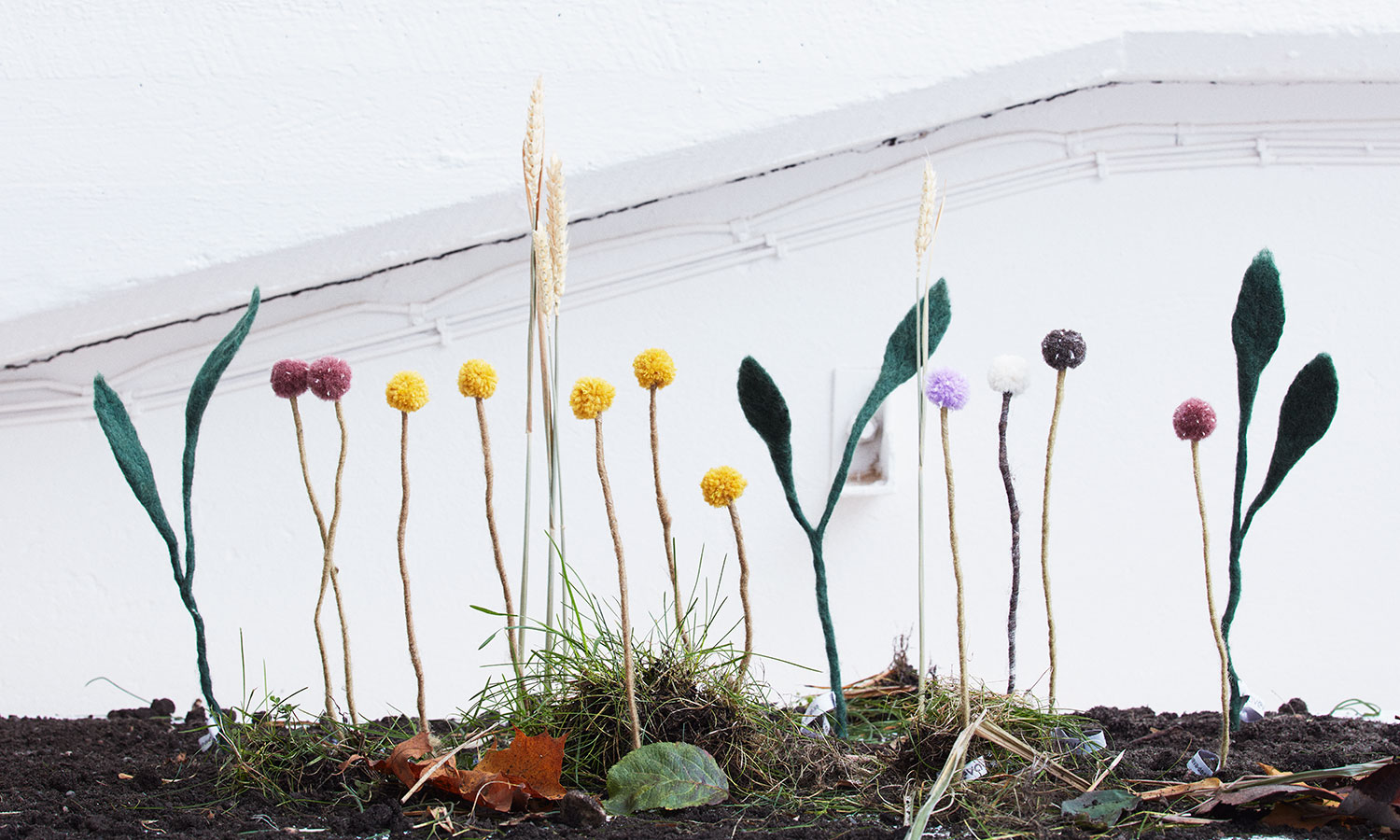 Green plants in wool pots in the colors sand and terracotta. Cut flowers in wool in different models that stand up in a flower bed.