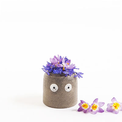Gray vase in ceramic with eyes, decorated with purple flowers.
