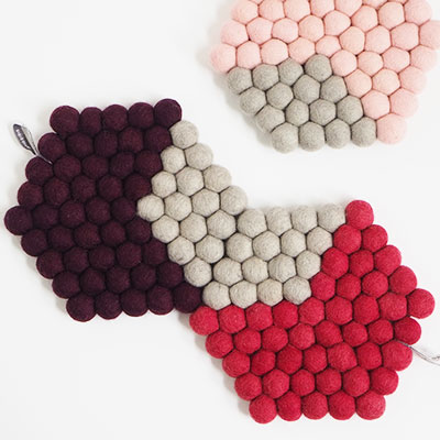3 hexagon shaped trivets made of 100% wool in aubergine, pink and raspberry.