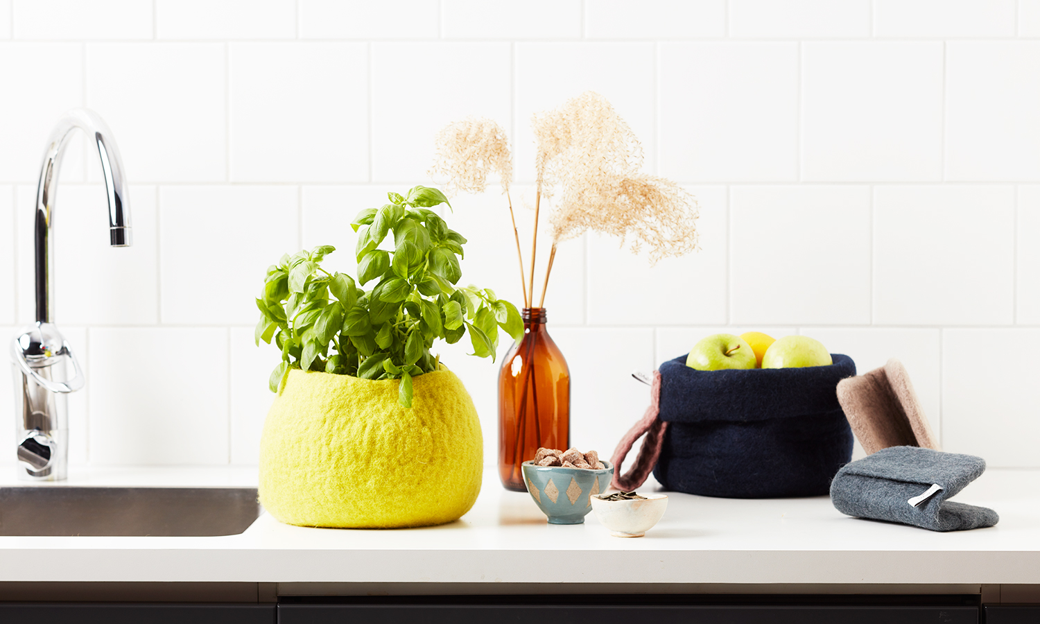 Grey and beige pot holders in kitchen with yellow flower pot