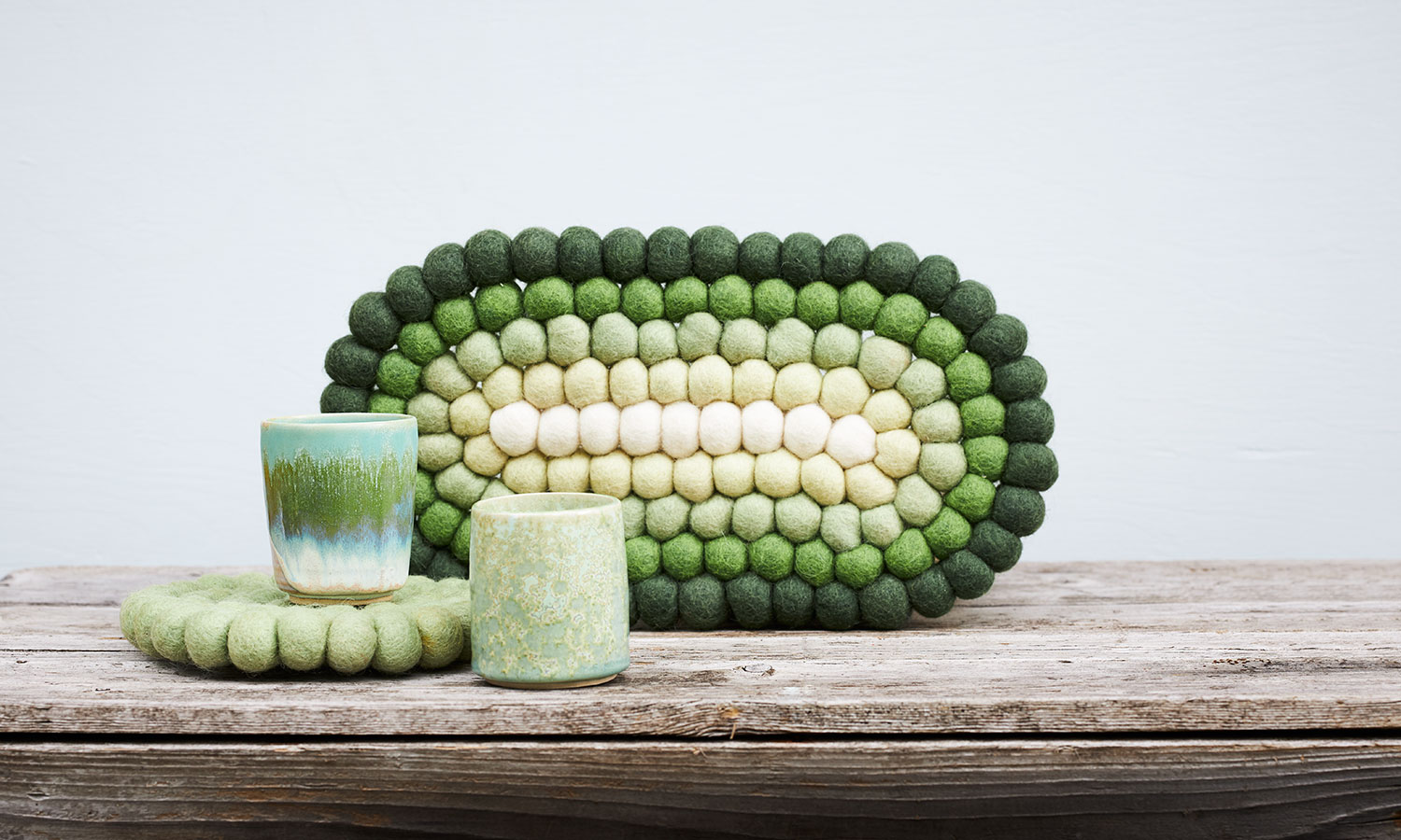 Oval and round wool trivets in green light shades, together with ceramic cups in the same green shade.