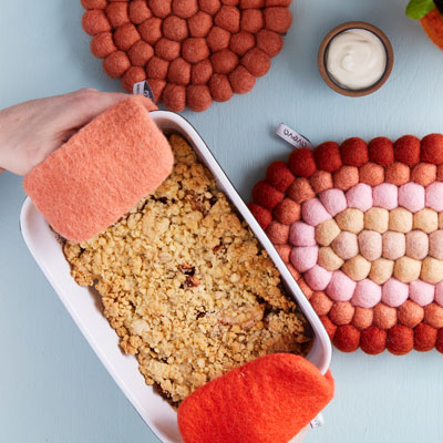 Potholders in terracotta and rust red color that hold in an oven dish.