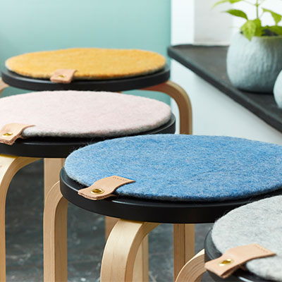 Seat cushions in wool with leather details, lying on chairs.