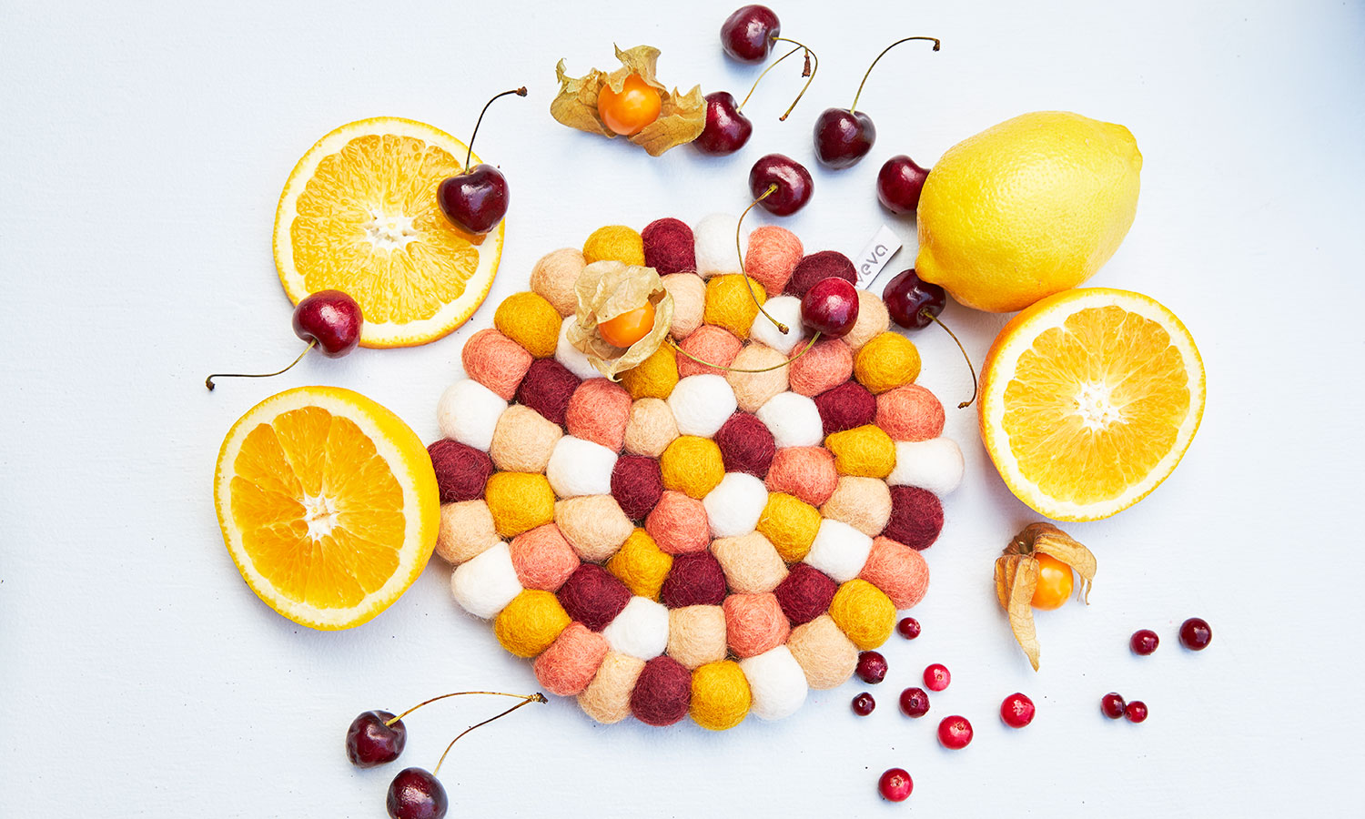 Round trivet in mixed colors with placed citrus fruits and berries next to the trivet.