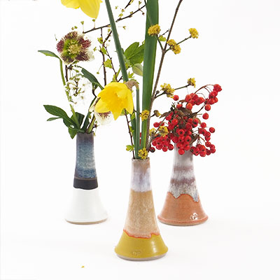 Vases in ceramic in different colors and glazes, filled with beautiful flowers.