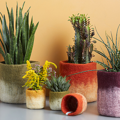 A set of flower pots in wool in different colors and sizes.