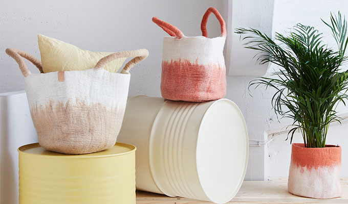 Baskets in wool in the colors sand and terracotta. The baskets have long handles and are designed with an ombre effect.