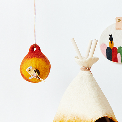 Bird house in rust and orange made of 100% wool.