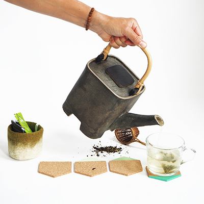 Hexagon coasters of light cork dipped in green with pitcher pouring tea.