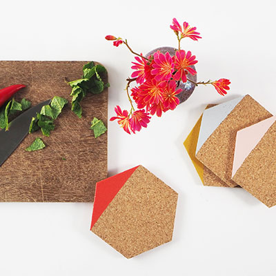 Coasters in light cork dipped in different colors, such as pink, mustard, red and grey.
