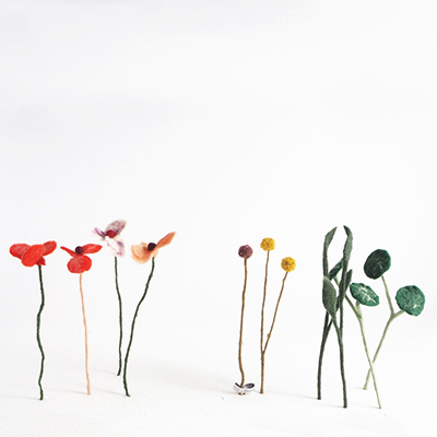Cut flowers in wool in different models that stand up in a flower bed.