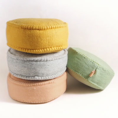 Floor cushions in wool in different pastel colors that lie in a pile.