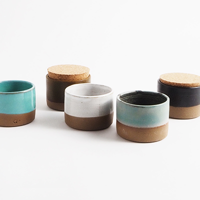 Jars in ceramic with a lid of light cork standing next to each other in different colors.
