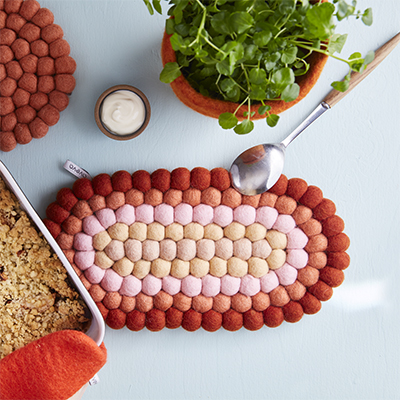 Oval trivet in 100% wool in pink, rust, terracotta and beige.