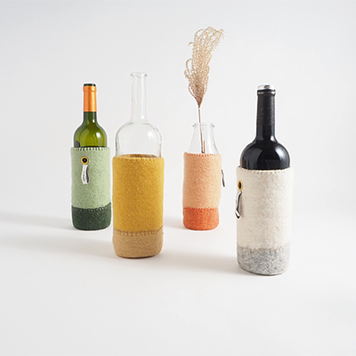 Wool container for bottles in shades of terracotta, ochre, white and green.