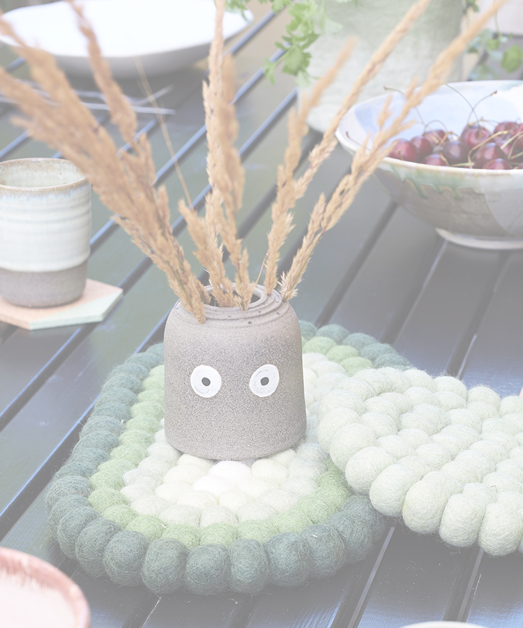 Gray vase in ceramic with a face, decorated with dried flowers on a table set outdoors.
