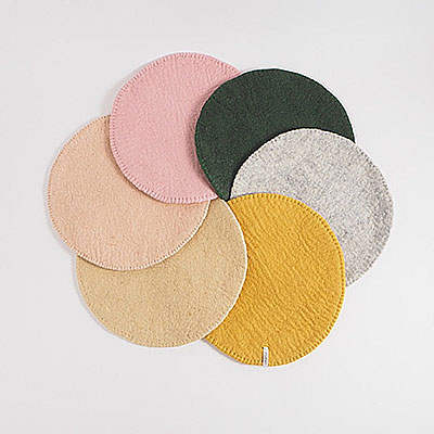 Seat cushions in wool with a stitched edge, lying in a round circle.