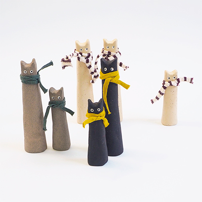 Collection of unique cats made in raw stoneware. White, gray and black. Have a scarf around the neck.