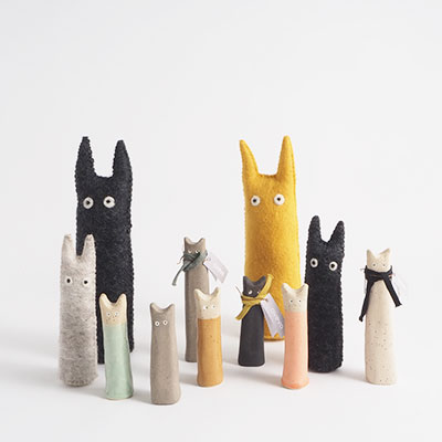 Cats in wool and ceramic in the colors black, gray, yellow, turquoise, sand and coral. The cats stand in a group together.