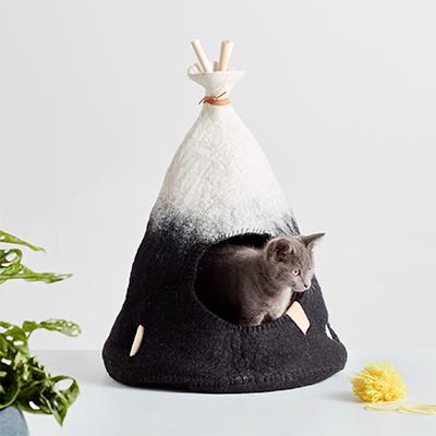 Litet handgjort tipitält i naturvit och svart ombre med en grå kattunge.
