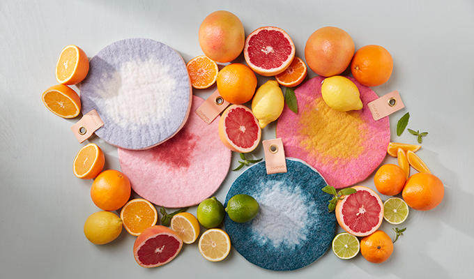 Round trivet in ombre with placed citrus fruits next to the trivet.