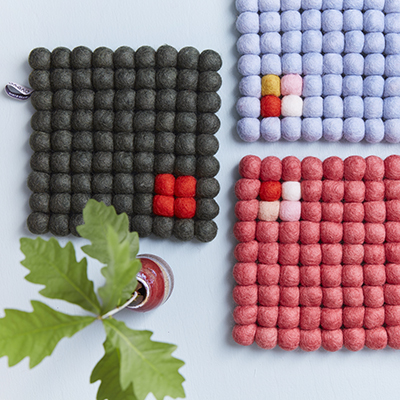 Square trivets of 100% wool - Dark gray, light blue and raspberry red, placed next to each other.
