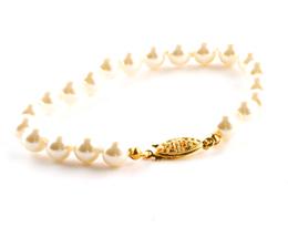 Armand med vita pärlor guldfärgat lås