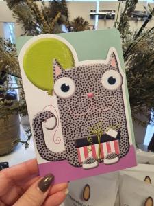 Kort med en festlig katt som håller i en grönglittrig ballong + paket, Pictura