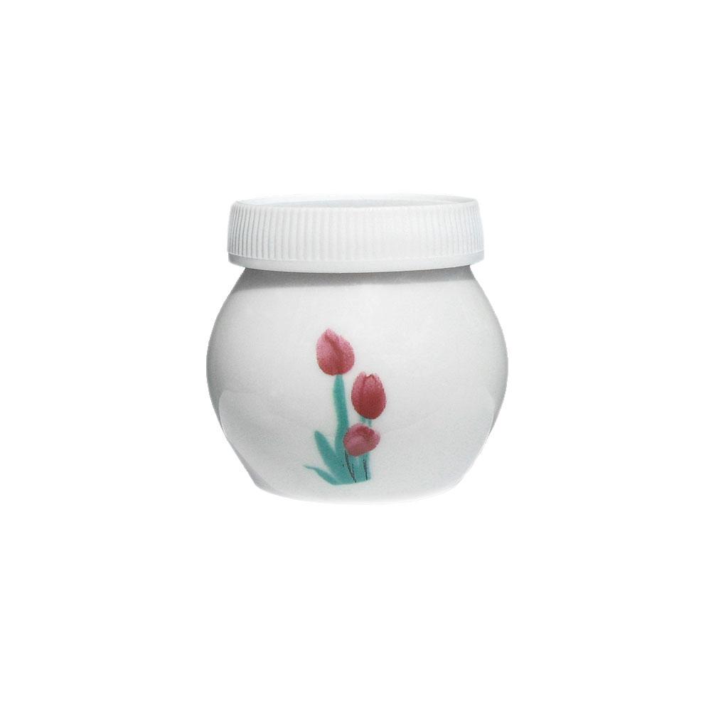 Dappenglas i vitt porslin med tulpaner på, inklusive vitt plastlock. 4 x 4 cm.