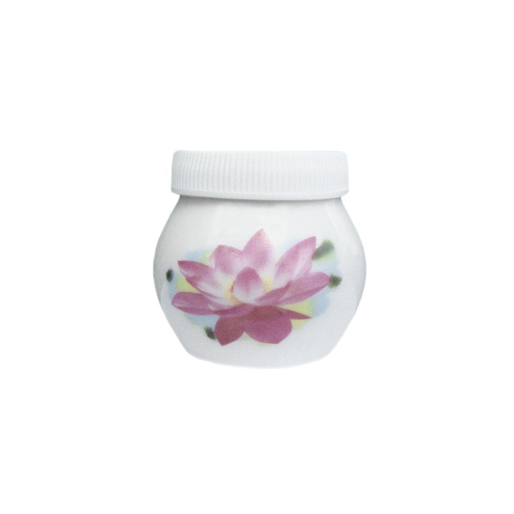 Dappenglas i vitt porslin med näckros på, inklusive vitt plastlock. 4 x 4 cm.