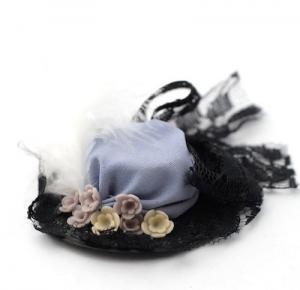Hatt i lilablått med svarta detaljer, blommor o fjäder