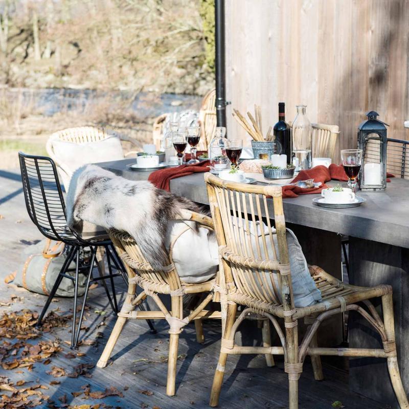 svart william i metall stor vid ett bord blandat med rottingstolar