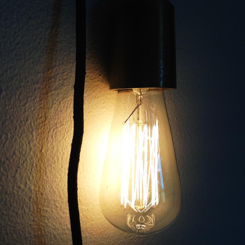 svart lamphållare med en tänd Edison lampa