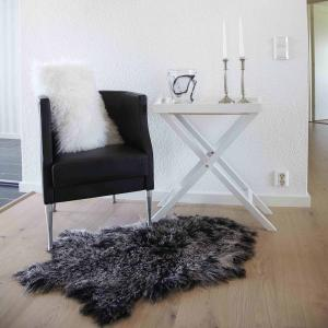 svart spräckligt tibetanskt lammskinn ligger på golvet framför en stol