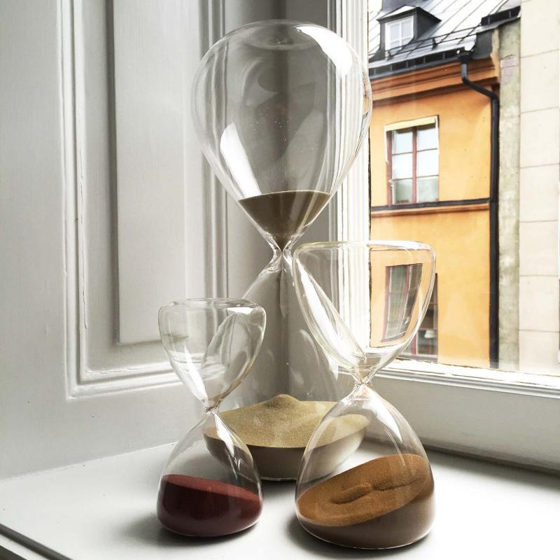 timglas med färgad sand stående i ett fönster