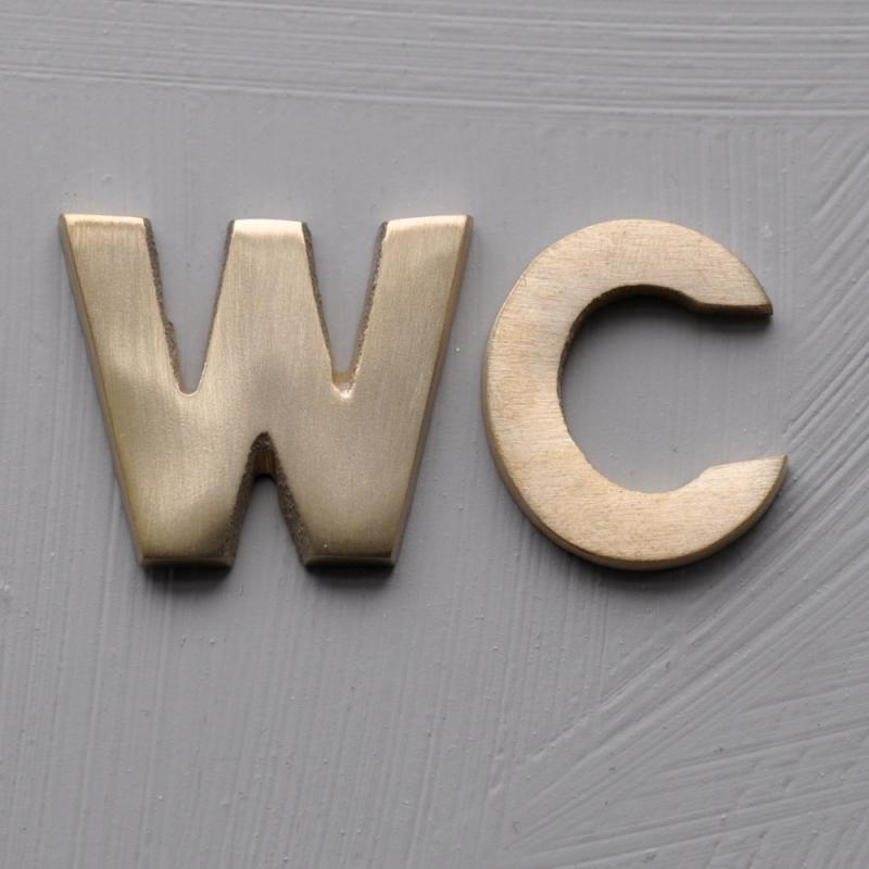 WC - bokstäver i borstad mässing